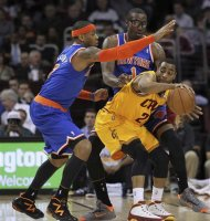 New York Knicks&#39; Carmelo Anthony (L) and Amar&#39;e Stoudemire (1) defend Cleveland Cavaliers&#39; Wayne Ellington (21) during the first quarter of their NBA basketball game in Cleveland March 4, 2013. REUTERS/Aaron Josefczyk