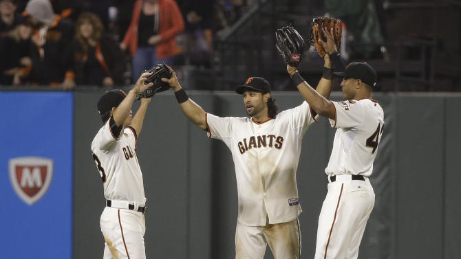 San Francisco Giants center fielder Angel Pagan, center, is greeted by teammates Nori Aoki, left, and Justin Maxwell at the end of a baseball game against the Atlanta Braves on Thursday, May 28, 2015, in San Francisco. San Francisco won 7-0. (AP Photo/Eric Risberg)