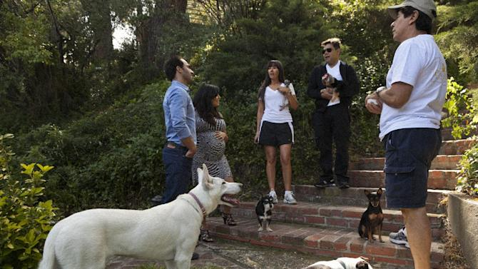 "In this photo taken Friday, May 11, 2012, entrepreneurs Aaron and Karine Hirschhorn, far left, interview with ""Paw Hills"" pet resort owners, the Sorrentini family right, at their home in Woodland Hills area of Los Angeles. Dog Vacay brings together responsible dog lovers with casual and professional dog sitters to provide an affordable experience for pets. (AP Photo/Damian Dovarganes)"