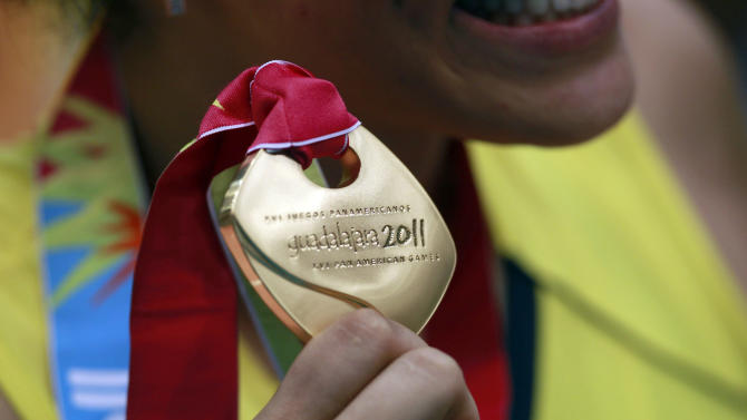 An unidentified player of Brazil shows off her gold medal after her team beat Cuba in the women's volleyball gold medal match during the Pan American Games in Guadalajara, Mexico, Thursday, Oct. 20, 2011. (AP Photo/Dario Lopez-Mills)