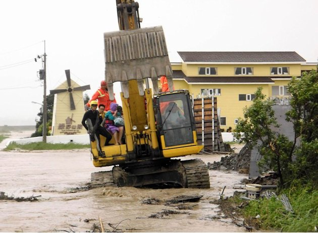 In this photo released by Hengchun Township Fire Department, residents are evacuated on an excavator as Typhoon Nanmadol began blowing toward Taiwan in Hengchu township, Pingtung county, southern Taiw
