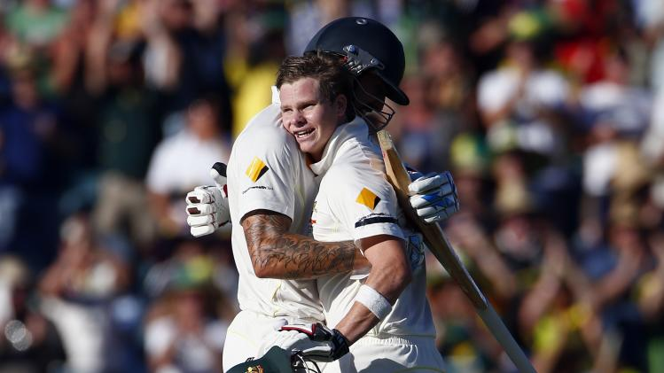 Australia's Smith hugs team mate Johnson after reaching his century during the first day of the third Ashes cricket test against England at the WACA ground in Perth