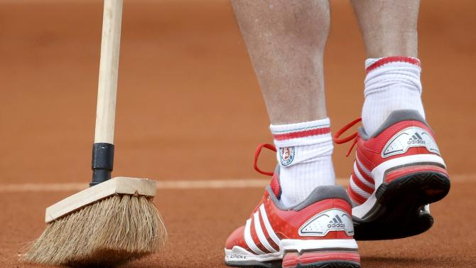 A court worker cleans the white lines during the women's singles match between Jelena Jankovic of Serbia and Sesil Karatantcheva of Bulgaria at the French Open tennis tournament at the Roland Garros stadium in Paris