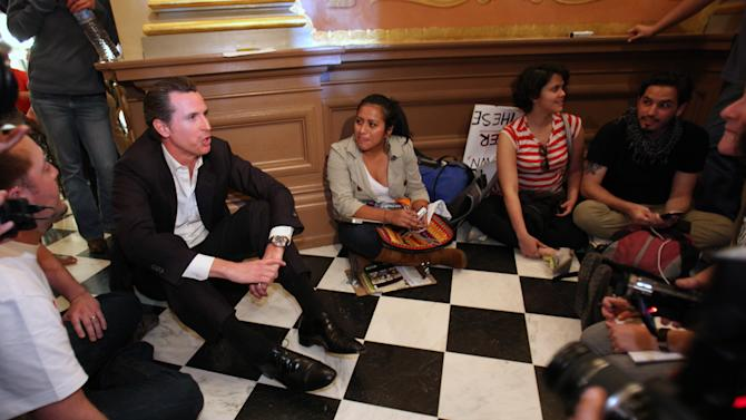 Lt. Gov. Gavin Newsom, left, sits down with protesters to discuss their demands for more funding for higher education during a sit-in against cuts to higher education held in the rotunda of the Capitol in Sacramento, Calif., Monday, March, 5, 2012.  Thousands of college students, teachers and supporters marched to the Capitol as part of a day long protest over state budget cuts to education.  The day was capped off with dozens of protesters were arrested after repeated warnings to leave the Capitol after it closed.  (AP Photo/Rich Pedroncelli)