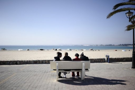 People sit on a bench facing the sea in Hammamet, Tunisia, in 2011. Tunisian blogger Sofiane Shurabi was arrested on Sunday for drinking alcohol in public at the beach during Ramadan with two friends, police and a lawyer said