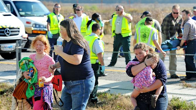 An family walks from the massive pile-up  accident on Interstate 10 in Southeast Texas Thursday Nov. 22, 2012.  The Texas Department of Public Safety says at least 35 people have been injured in a more than 50-vehicle pileup.    (AP Photo/The Beaumont Enterprise, Guiseppe Barranco)  Mandatory Credit