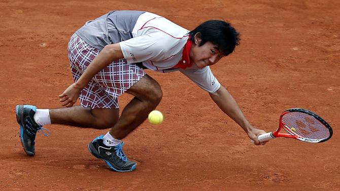 Japan's Yoshihito Nishioka reaches for the ball as he plays zech Republic's Tomas Berdych during their first round match of the French Open tennis tournament at the Roland Garros stadium, Monday, May 25, 2015 in Paris,  (AP Photo/Michel Euler)