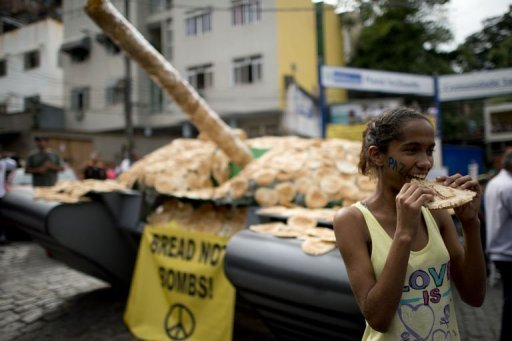 A girl in Rio eats bread next to a fake tank covered with bread - a protest against the weapons market
