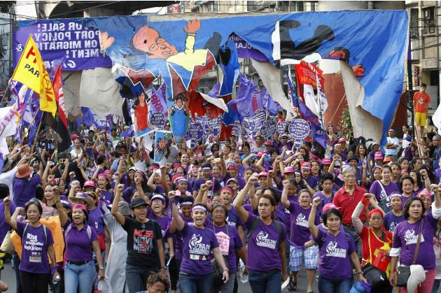 Members of women's group (GABRIELA) clench fists during an International Women's Day protest, while marching towards the presidential palace in Manila