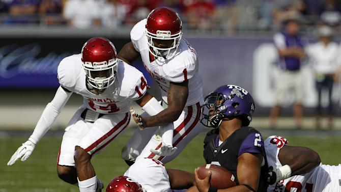Oklahoma's Aaron Colvin (14), Tony Jefferson (1), Frank Shannon, bottom left, and Stacy McGee (92) combine to bring down TCU quarterback Trevone Boykin (2) in the first half of an NCAA college football game Saturday, Dec. 1, 2012, in Fort Worth, Texas. (AP Photo/Tony Gutierrez)