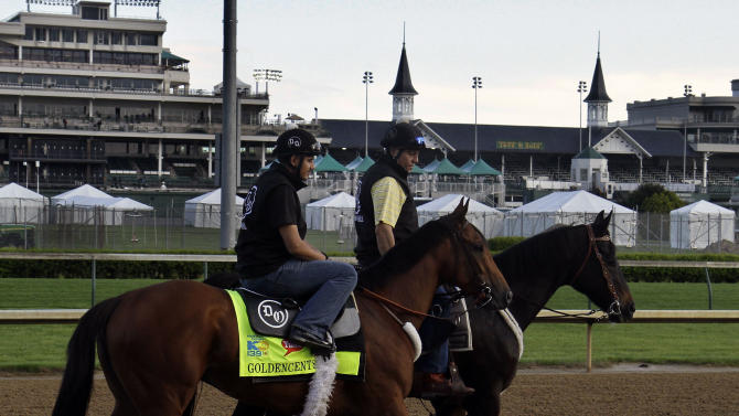 Kentucky Derby hopeful Goldencents, left, with exercise rider Jonny Garcia aboard, makes his first appearance on the track at Churchill Downs, Sunday, April 28, 2013, in Louisville, Ky. after arriving from California, Saturday. (AP Photo/Garry Jones)