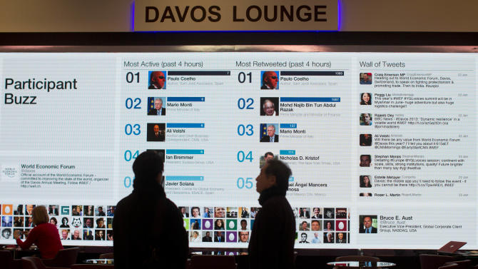 People gather at the 'Davos lounge'  inside the Congress Center and follow the latest tweets of participants on the eve of the opening of the 43rd Annual Meeting of the World Economic Forum, WEF, in Davos, Switzerland, Tuesday, Jan. 22, 2013. As corporate leaders gather for the World Economic Forum in Davos amid a slow and shaky recovery, a new study looks at business leaders' moods and what they hope to do this year.  (AP Photo/Anja Niedringhaus)