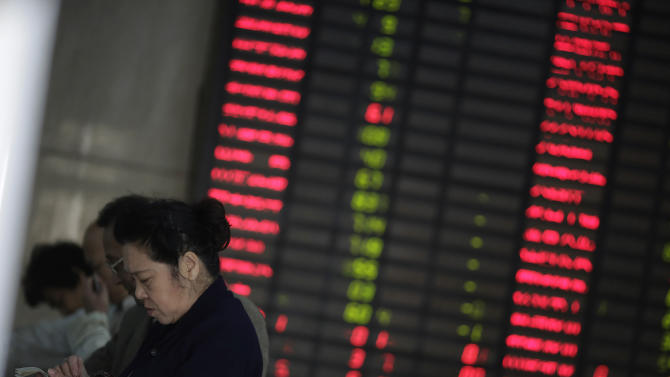 Investors check the stock price at a private securities company in Shanghai, China on Tuesday Nov. 13, 2012. Asian stock markets fell Tuesday, after Europe's finance ministers postponed approval of an urgently needed aid payment for debt-mired Greece. (AP Photo/Eugene Hoshiko)