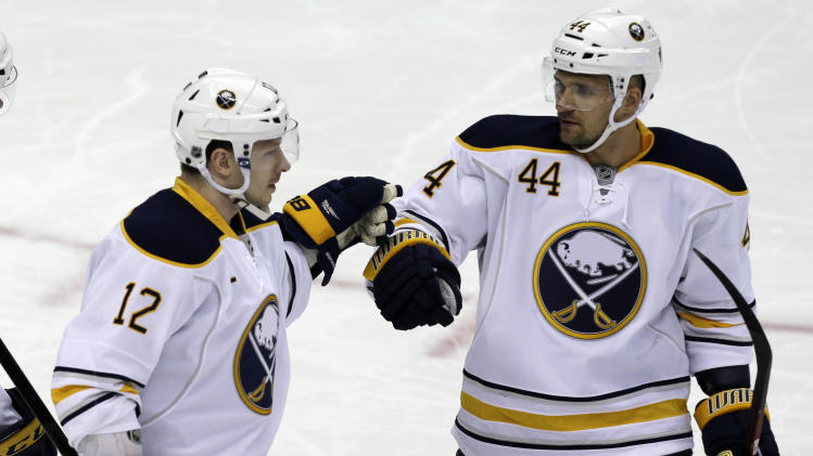 Buffalo Sabres center Kevin Porter (12) celebrates his first-period goal with defenseman Andrej Sekera (44) during an NHL hockey game against the Pittsburgh Penguins in Pittsburgh Tuesday, April 2, 2013. (AP Photo/Gene J. Puskar)