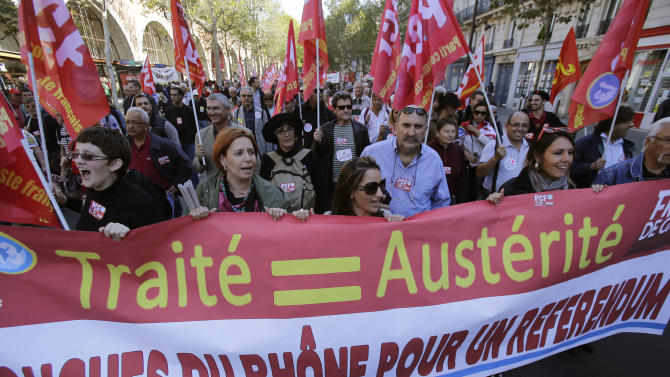 """Demonstrators march during a rally holding a banner which reads,""""treaty equal austerity, Bouches du Rohne region for a referendum"""", to protest against the austerity measures announced by the French government, in Paris, Sunday, Sept 30, 2012. (AP Photo/Michel Euler)"""