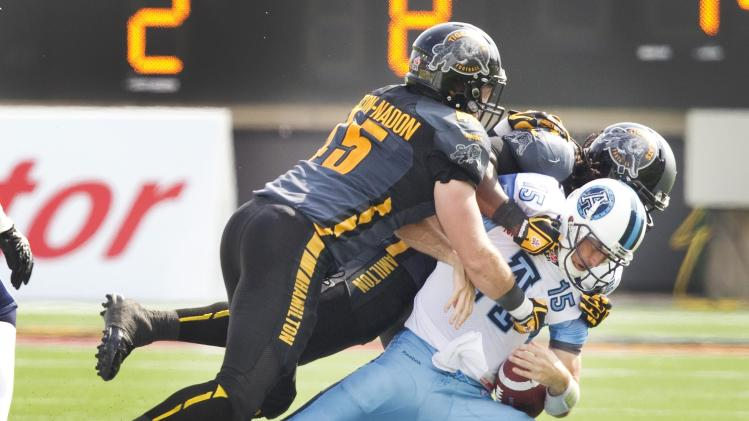Argonauts' Ray is sacked by the Tiger-Cats' Gascon-Nadon and Reed in their CFL Labour Day Classic football game in Hamilton
