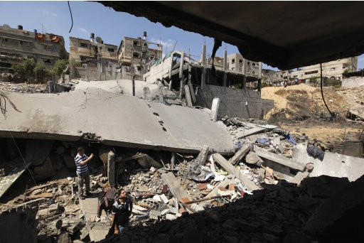 Palestinians stand on rubble after an Israeli air strike in Beit Lahiya