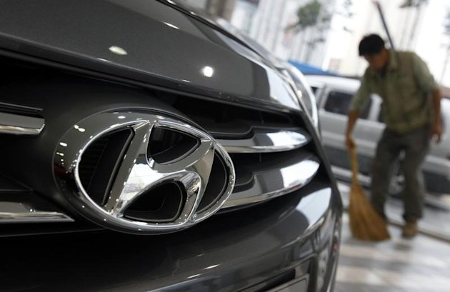 The logo of Hyundai Motor is seen on the on a car as a worker sweeps a floor at a Hyundai dealership in Seoul October 25, 2012. REUTERS/Kim Hong-Ji/Files