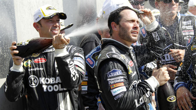 Jimmie Johnson, right, gets doused by crew chief Chad Knaus after winning the NASCAR Sprint Cup Series Brickyard 400 auto race at Indianapolis Motor Speedway in Indianapolis, Sunday, July 29, 2012. (AP Photo/Tom Strattman)