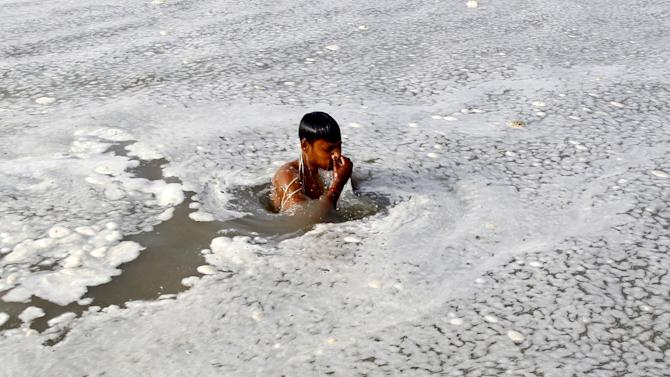 A Hindu devotee takes a dip in the polluted water of the Ganges river in Allahabad