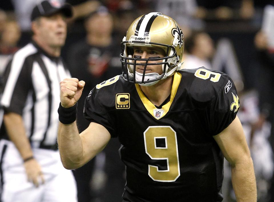 New Orleans Saints quarterback Drew Brees celebrates his touchdown pass to wide receiver Robert Meachem  in the third quarter of an NFL football game against the New Orleans Saints in New Orleans, Monday, Dec. 26, 2011. (AP Photo/Bill Haber)
