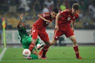 Emre Can (C) and Thomas Muller (R) of Bayern Munich take the ball from Mao Jianqing (L) of Beijing Guoan during a friendly match in Beijing. Bayern Munich beat Guoan 6-0