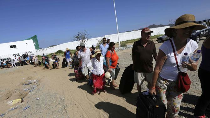 Stranded tourists wait for a Mexican Army plane that will transport them, outside the international airport in San Jose del Cabo after Hurricane Odile hit in Baja California,