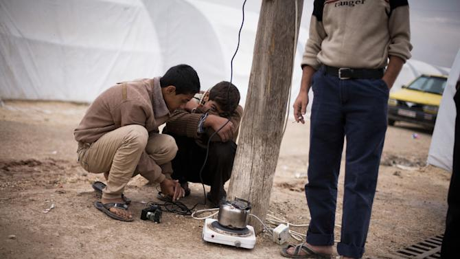 Two displaced young Syrians heat a tea pot  in a refugee camp near Azaz, Syria, Tuesday, Oct. 23, 2012. (AP Photo/ Manu Brabo)