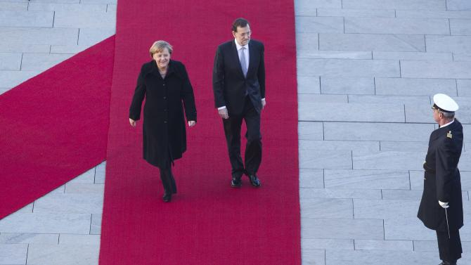 German Chancellor Angela Merkel, left, welcomes Spain Prime Minister Mariano Rajoy, center,  for talks at the chancellery in Berlin, Germany, Thursday, Jan. 26, 2012. (AP Photo/Markus Schreiber)