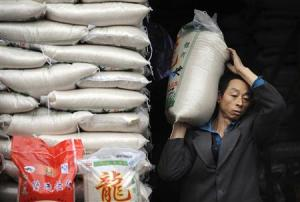 File photo of a worker transporting packs of rice at a market in Hefei, Anhui province