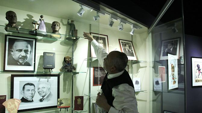 In a March 14, 2012 photo, David Pilgrim, the founder and curator who started building the Jim Crow Museum of Racist Memorabilia, adjusts a display at the museum in Big Rapids, Mich. The museum says it has amassed the nation's largest public collection of artifacts spanning the segregation era, from Reconstruction until the civil rights movement, and beyond. (AP Photo/Carlos Osorio)
