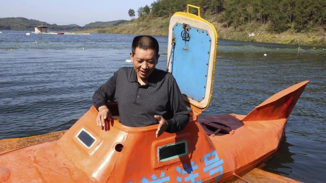 Tan Yong finishes diving his home-made submarine at a lake in Dangjiangkou