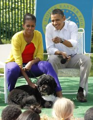 U.S. President Barack Obama and first lady Michelle Obama sit with their dog Bo during a book reading session with children during the annual White House Easter Egg Roll in Washington April 9, 2012.   REUTERS/Jason Reed (UNITED STATES - Tags: POLITICS)
