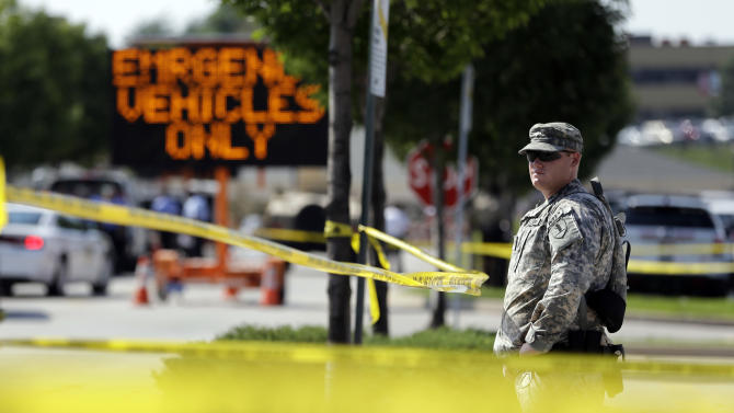 "A member of the Missouri National Guard stands guard at a police command post Tuesday, Aug. 19, 2014, in Ferguson, Mo. Ferguson's leaders urged residents Tuesday to stay home after dark to ""allow peace to settle in"" and pledged several actions to reconnect with the predominantly black community in the St. Louis suburb where the fatal shooting of 18-year-old Michael Brown has sparked nightly clashes between protesters and police. (AP Photo/Jeff Roberson)"