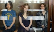 "The three members of the Russian punk band ""Pussy Riot"" -- Nadezhda Tolokonnikova (left), Maria Alyokhina (centre) and Yekaterina Samutsevich -- sit inside a glass enclosure during a court hearing in Moscow"