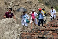 Chinese rescue workers walk past a landslide site as rocks continue to fall after a series of earthquakes in Yunnan Province