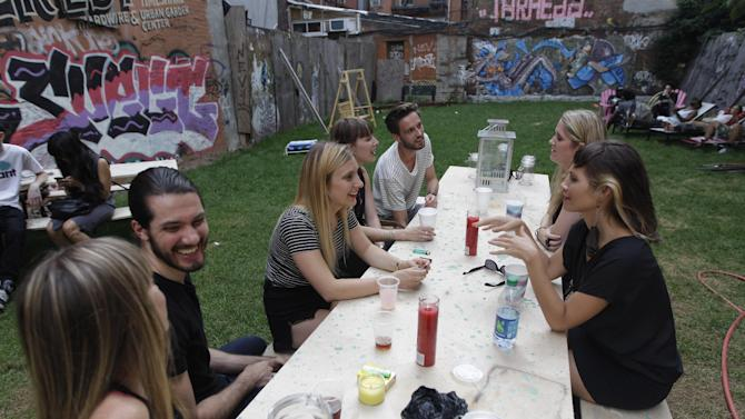 In this Wednesday, July 25 2012 photo, a group of people hang out at a picnic table at Timeshare Backyard on the Lower East Side of Manhattan. The city's lone timeshare backyard allows New Yorkers to invite up to 30 guests for two hours at a time and comes with grills, lounge chairs and trashy magazines.  (AP Photo/Mary Altaffer)