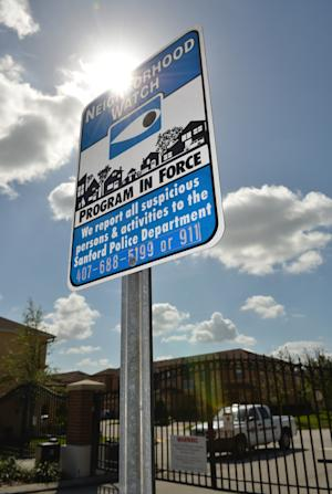 FILE - In this March 23, 2012 file photo, a Neighborhood Watch warning sign is posted outside The Retreat at Twin Lakes gate in Sanford, Fla. The Retreat at Twin Lakes is where 17-year-old Trayvon Martin was shot and killed by neighborhood watch captain George Zimmerman on Feb. 26, 2012. If Martin's family sues over his death, they might not target George Zimmerman but the homeowners association of the neighborhood where the shooting happened and Zimmerman lived. (AP Photo/Roberto Gonzalez, File)