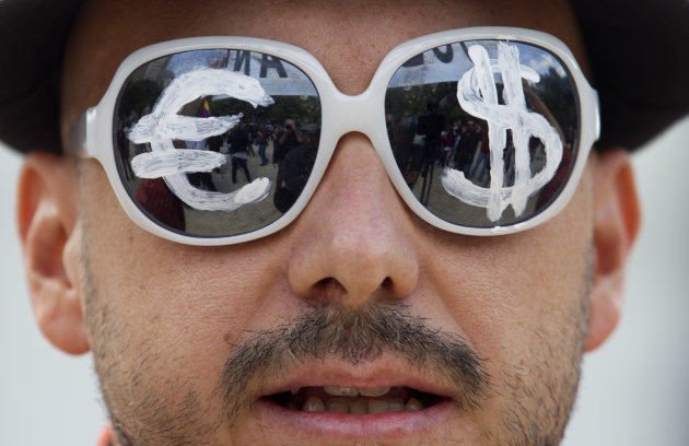 <p>               FILE - In this Tuesday, Sept. 25, 2012 file photo, a protester wears glasses with the euro and dollar symbols painted on the lenses before protesting the conservative government's handling of the economic crisis and to demand fresh elections, in Madrid. Many had hoped that 2012 would be the year when the global economy finally regained its vigor, but the three largest economies: The United States, China and Japan struggled, while the 17 countries that use euro endured a third painful year in their financial crisis and slid into recession, and emerging economies slowed. (AP Photo/Paul White, File)