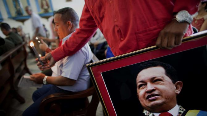 """A Venezuelan embassy worker holds a framed image of Venezuela's ailing President Hugo Chavez during the monthly Catholic service devoted to the sick at the Church of Our Lady of Regla, in Regla, across the bay from Havana, Cuba, Tuesday, Jan. 8, 2013. Venezuela's government said Monday, Chavez is in a """"stable situation"""" in a Cuban hospital receiving treatment due to a severe respiratory infection. The update came as other government officials reiterated their stance that the president need not be sworn in for a new term as scheduled this Thursday and could instead have his inauguration at a later date. (AP Photo/Ramon Espinosa)"""