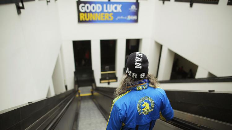 "An entrant in the 2014 Boston Marathon, wearing a jacket from the previous year's race as well as a hat with ""MR8"" on it, leaves after picking up his official race bib Boston"