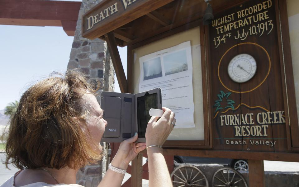 Laura McAlpine, of Scotland takes a picture of the thermometer at the Furnace Creek resort in Death Vally National Park Friday, June 28, 2013 in Furnace Creek, Calif. Excessive heat warnings will continue for much of the Desert Southwest as building high pressure triggers major warming in eastern California, Nevada, and Arizona. (AP Photo/Chris Carlson)
