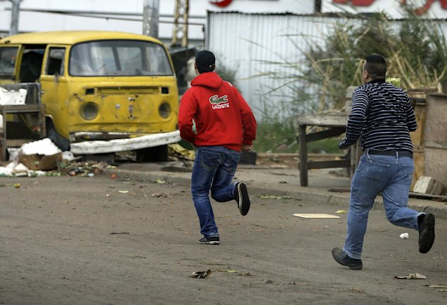 Lebanese citizens run to cross a street to avoid sniper fire during clashes that erupted between pro and anti-Syrian regime gunmen in the northern port city of Tripoli, Lebanon, Wednesday, Dec. 5, 2012. Gunmen loyal to opposite sides in neighboring Syria's civil war battled in the streets of northern Lebanon and the death toll from two days of fighting was at least five killed and 45 wounded, officials said. The fighting comes at a time of deep uncertainty in Syria, with rebels closing in on President Bashar Assad's seat of power in Damascus. (AP Photo/Hussein Malla)
