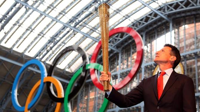 Sebastian Coe, Chairman of the London 2012 Olympic Organising Committee, poses with the newly unveiled 2012 London Olympic Torch, at St Pancras International Rail Station, central London, on June 8, 2011