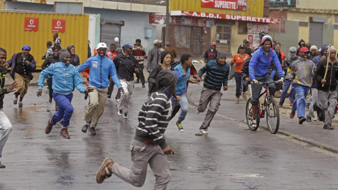 Farm workers run away from Police during a demonstrate due to low wages in the town of Grabouw, South Africa, Wednesday, Jan 9, 2013. Striking farm workers on Wednesday set up barricades and threw stones at motorists and police in a South African province whose vineyards are vital to the wine industry, prompting riot officers to close roads and arrest at least 50 demonstrators, South African media reported. (AP Photo/Schalk van Zuydam)