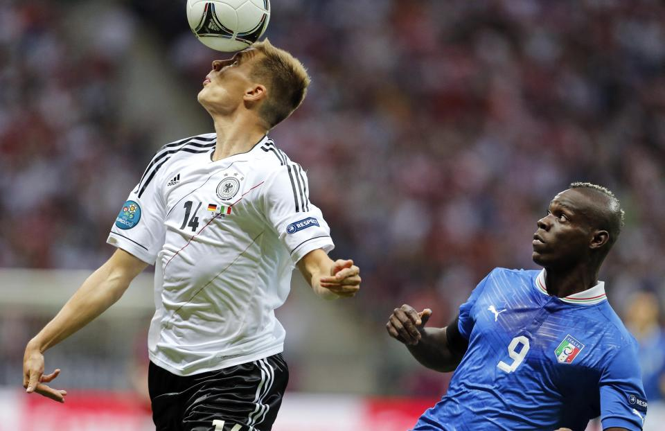 Germany's Holger Badstuber heads the ball in front of Italy's Mario Balotelli during the Euro 2012 soccer championship semifinal match between Germany and Italy in Warsaw, Poland, Thursday, June 28, 2012. (AP Photo/Gregorio Borgia)