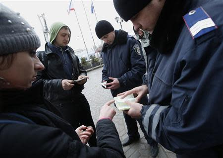 Policemen check the passports of passengers at the railway station in Simferopol