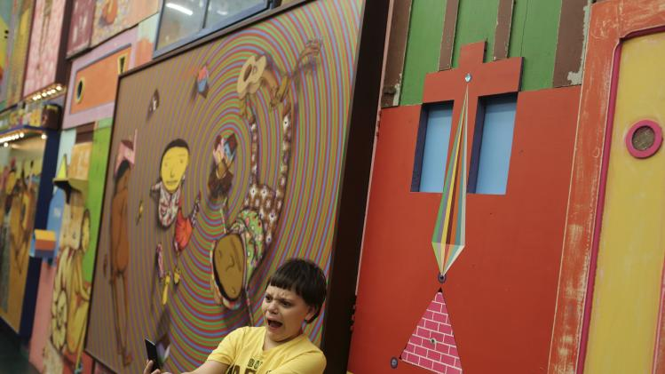 "Boy takes a ""selfie"" in front of artworks by Brazilian artists and twin brothers, who go by the name ""Os Gemeos"", during their exhibition ""Opera of the Moon"" in Sao Paulo"