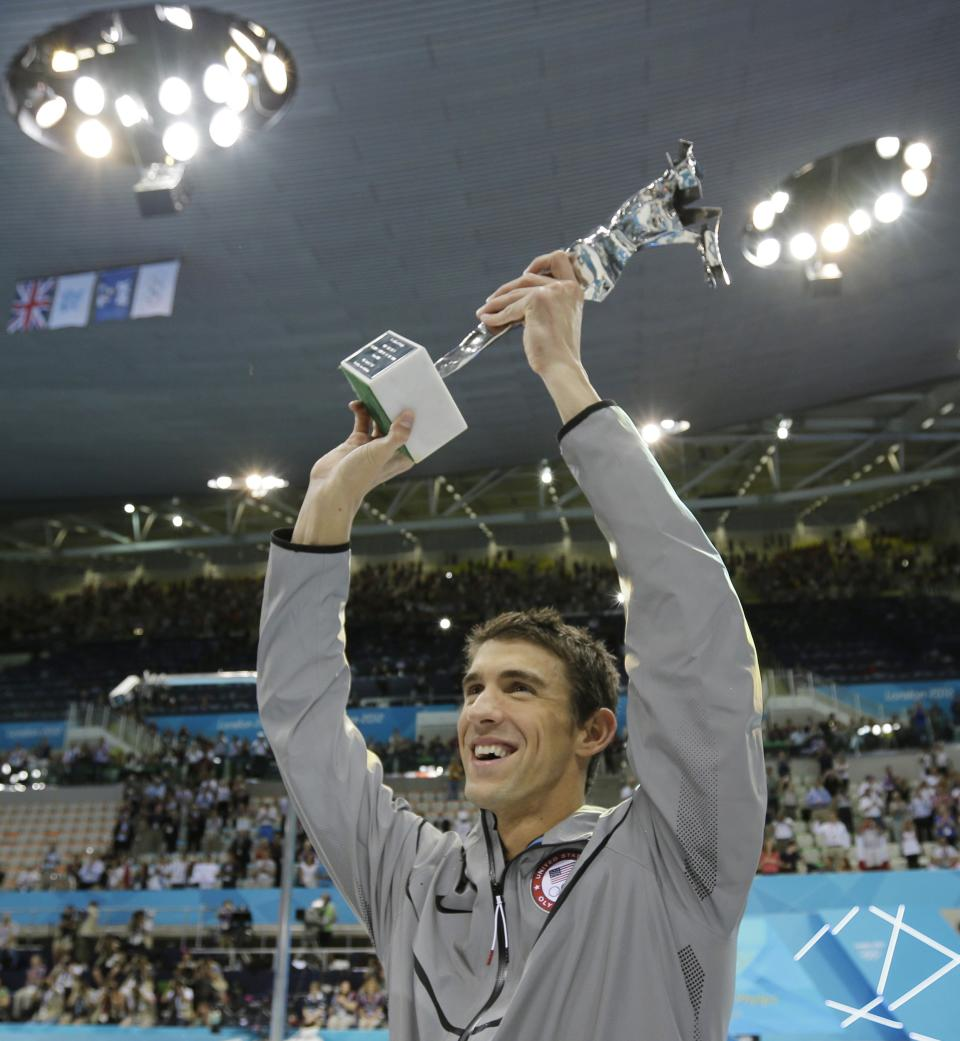 United States' swimmer Michael Phelps holds up a silver trophy after being honored as the most decorated Olympian at the Aquatics Centre in the Olympic Park during the 2012 Summer Olympics in London, Saturday, Aug. 4, 2012. (AP Photo/Matt Slocum)