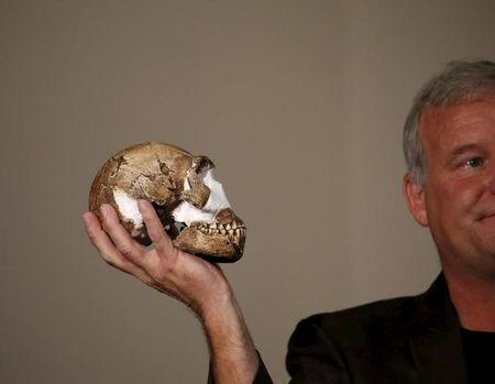"Professor Lee Berger holds a replica of the skull of a newly discovered ancient species, named ""Homo naledi"", during its unveiling outside Johannesburg"